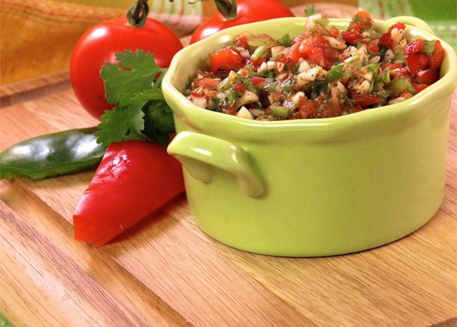 a pale green ramekin of sofrito tih cilantro, tomatoes, and red pepper on the side