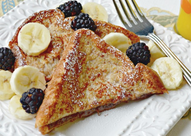 Slices of diagonally-cut French toast dusted with powdered sugar, on a plate with banana slices and fresh blackberries