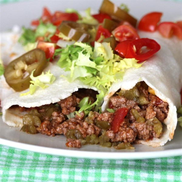 side view of two burritos filled with ground beef, topped with shredded lettuce and jalapeno slices