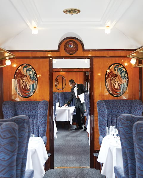 Inside a car of the Belmond British Pullman train, with blue upholstered seats, tables with white tablecloths, and wood parquet paneling on walls