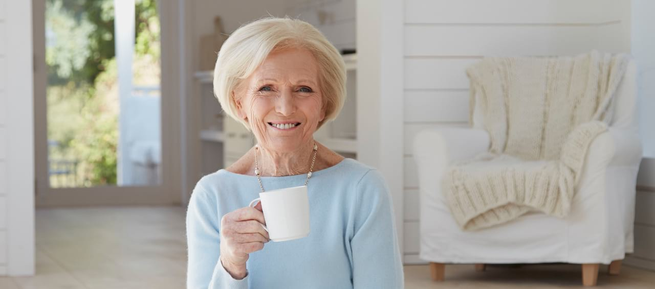 Mary Berry in light blue sweater sitting in kitchen with shiplap walls holding up a white coffee cup