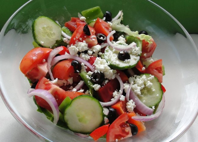 A salad of sliced cucumbers, red onion, red bell pepper, olives, and crumbled feta on a glass plate