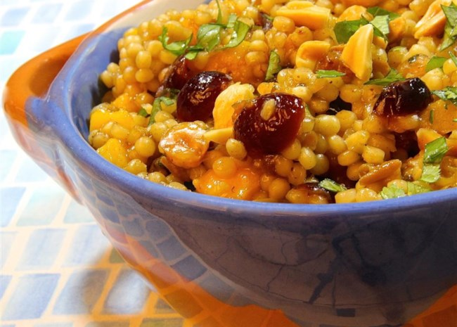 closeup of couscous and dried fruit in a blue bowl