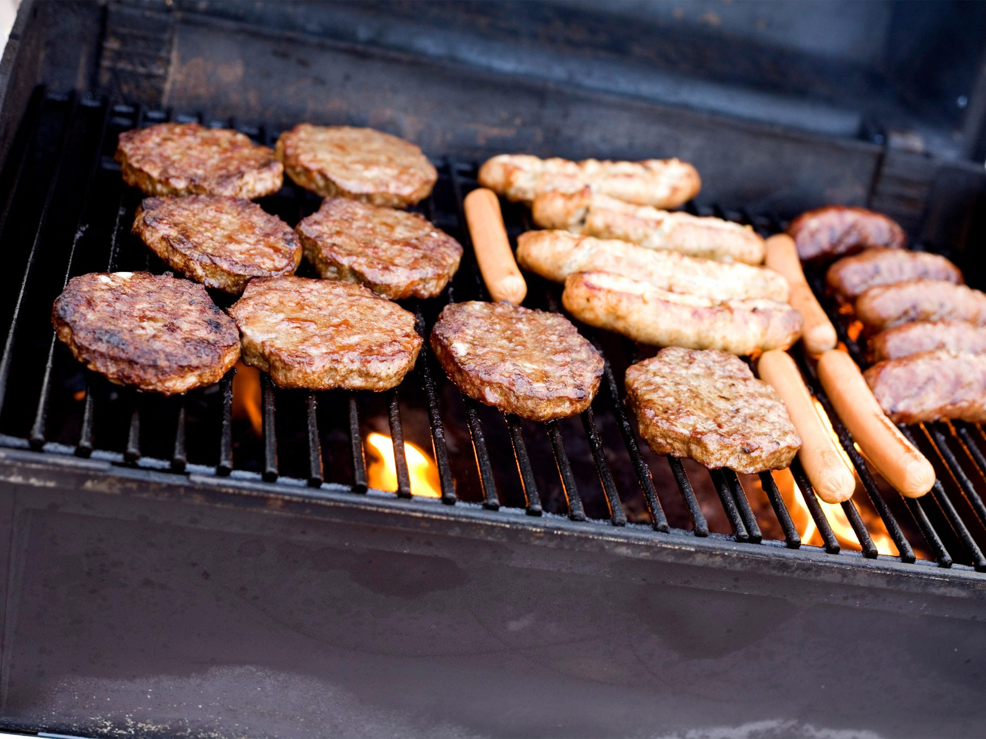 Hamburgers and hot dogs on a gas grill