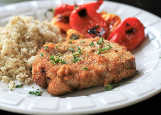 Crispy pork chops garnished with parsley on a plate with couscous and roasted mini bell peppers