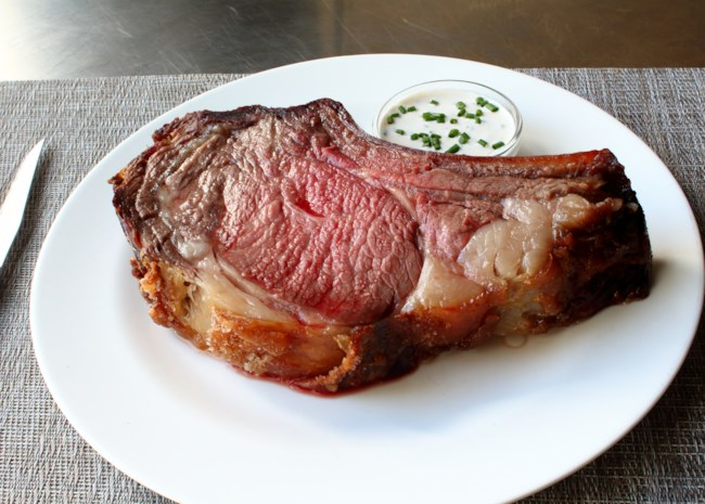 a slice of medium-rare prime rib on a white plate with horseradish sauce
