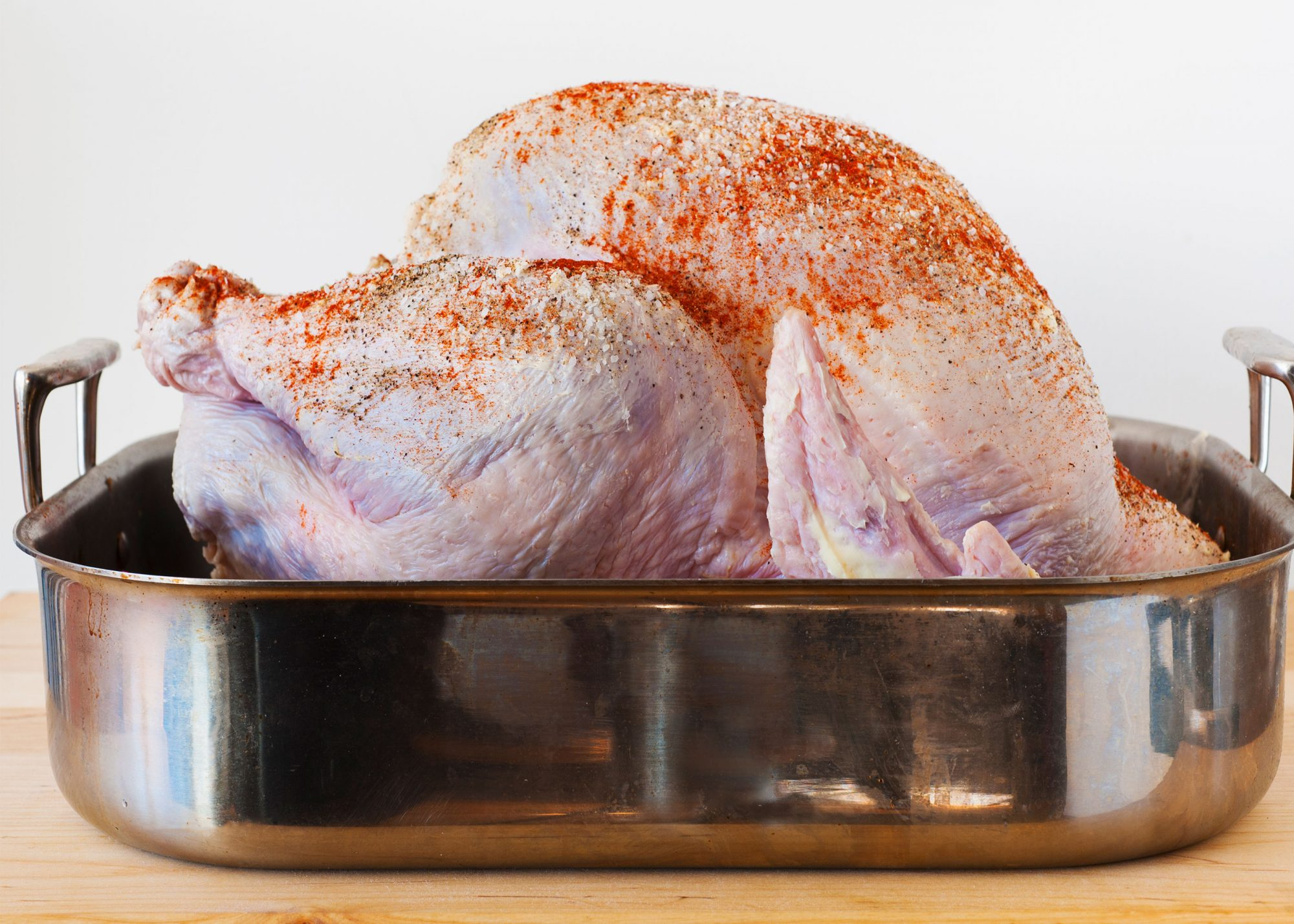 Unroasted turkey sprinkled with dry rub in a roasting pan