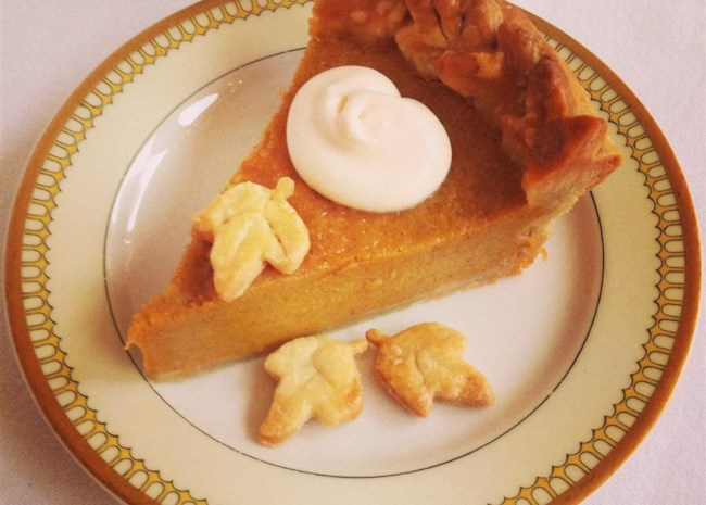 a top-down view of a slice of pumpkin pie garnished with pastry leaves and whipped cream