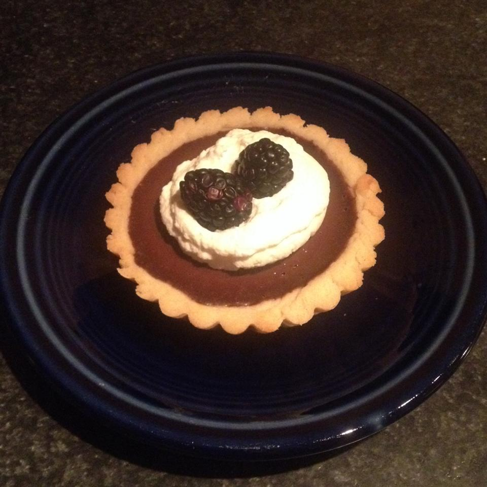 Rich Chocolate Tart topped with whipped cream and blackberries on a black plate