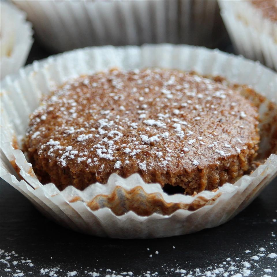 pumpkin cheesecake cupcake topped with powdered sugar in a cupcake wrapper