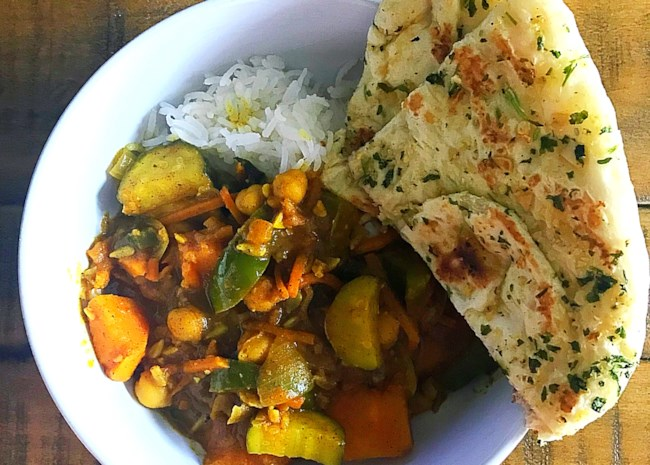 vegan vegetable curry over rice with naan