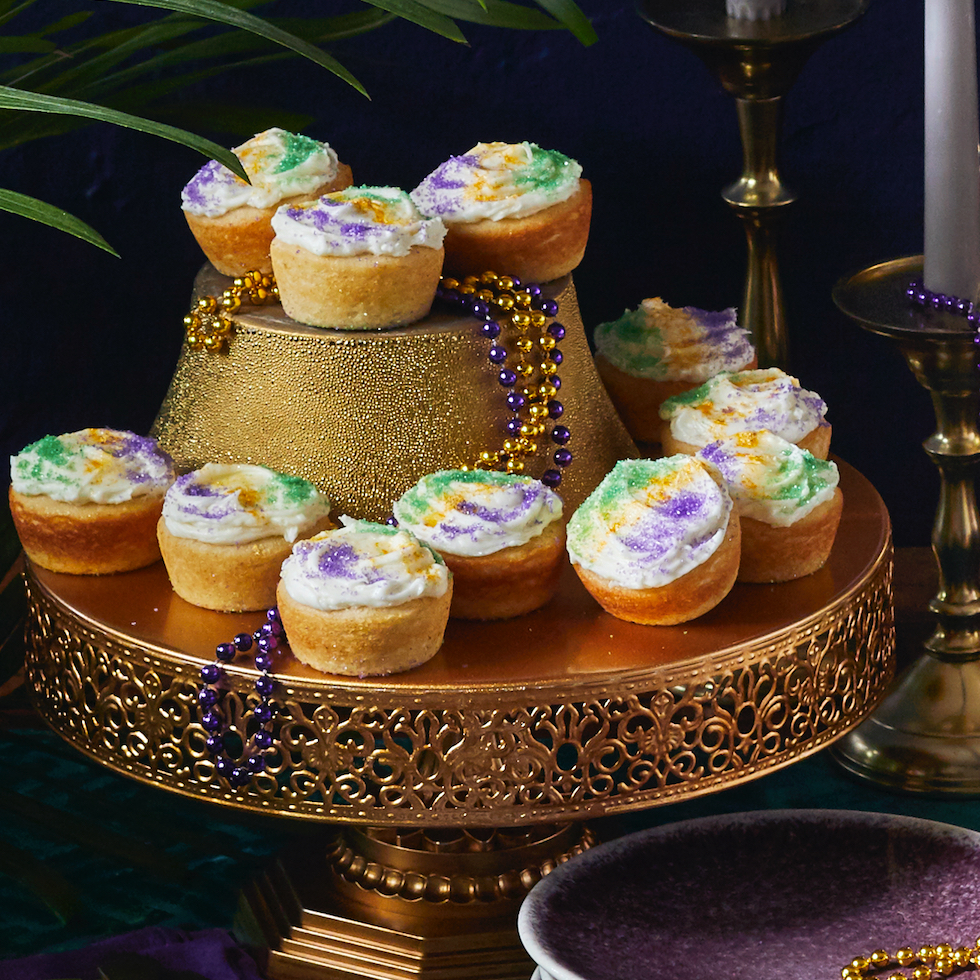 king cake cupcakes on a stand with mardi gras beads