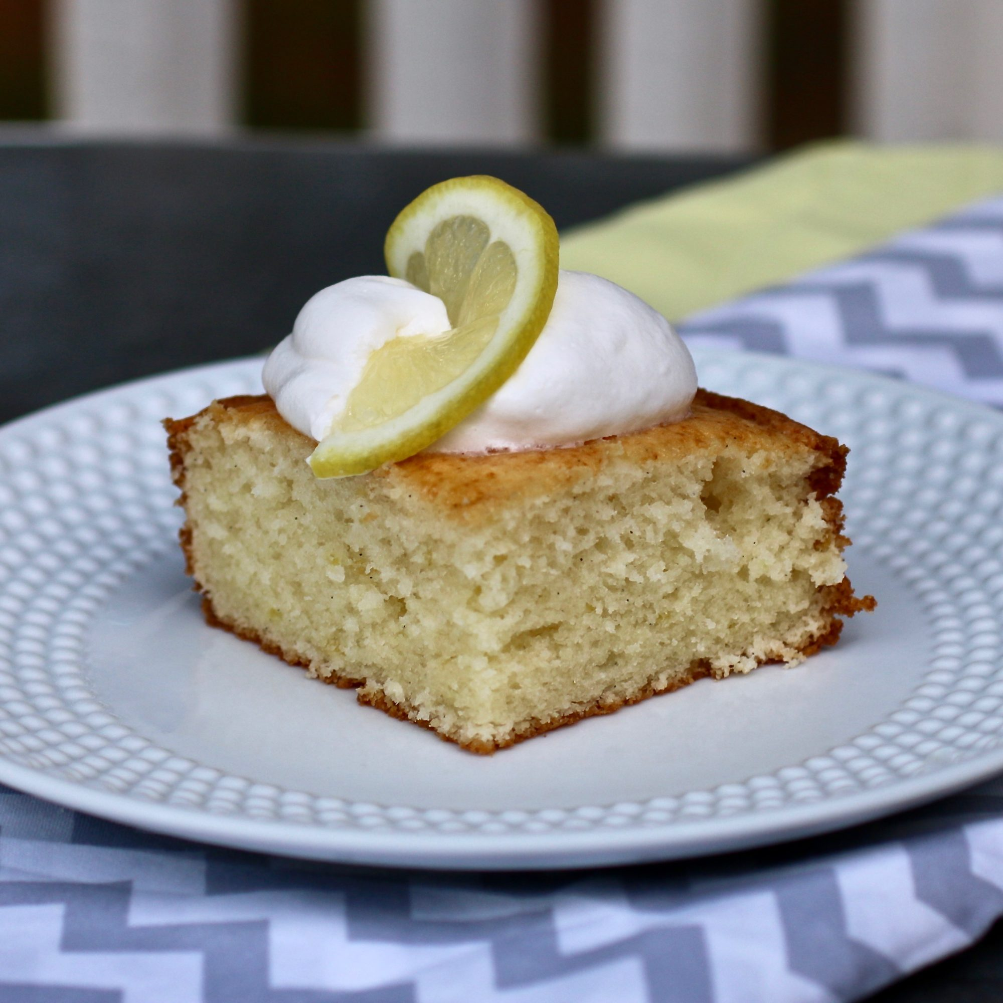 slice of lemon caked topped with whipped cream and lemon