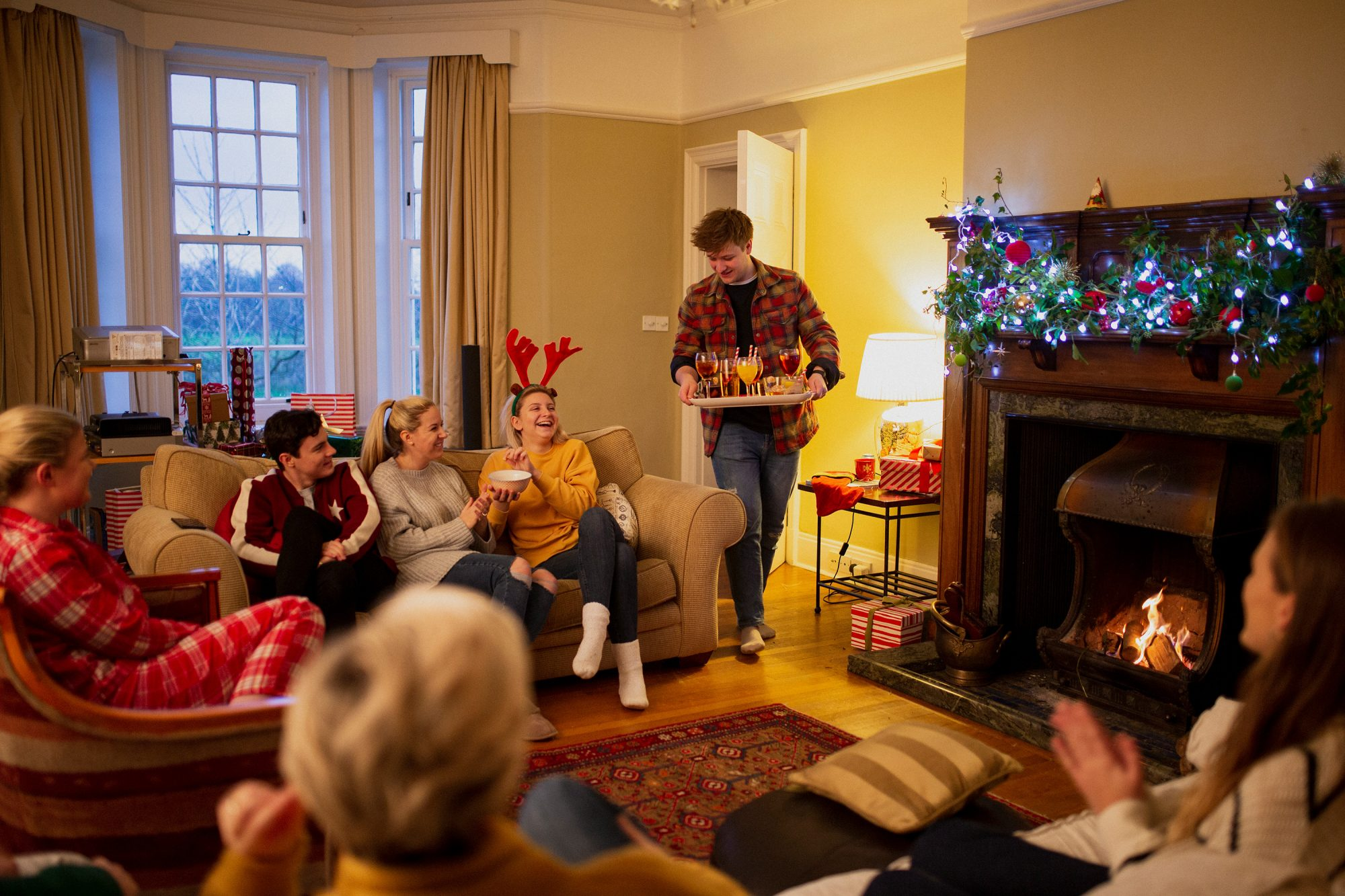 One young man is serving drinks to his friends at a Christmas house party.