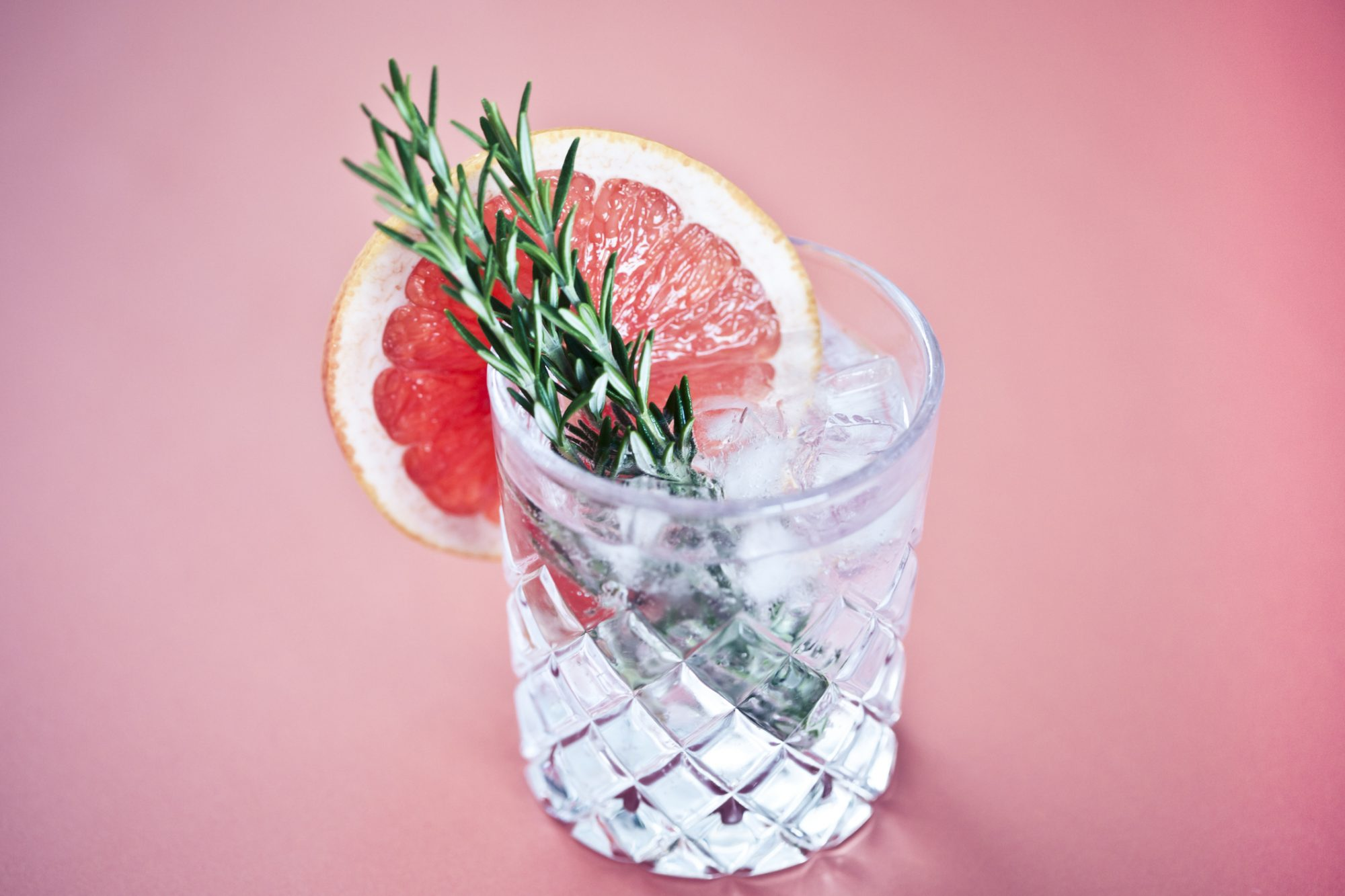 Close-up of a glass of gin and tonic with a slice of pink grapefruit and sprigs of rosemary on a white background.
