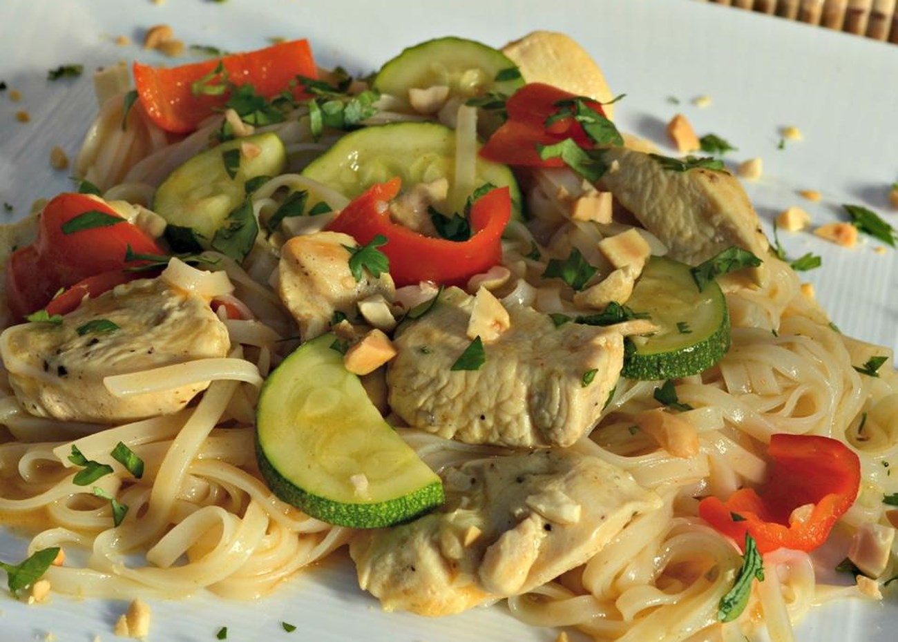 a colorful dish of wide rice noodles, zucchini, red bell pepper, chicken breast pieces, and chopped peanuts