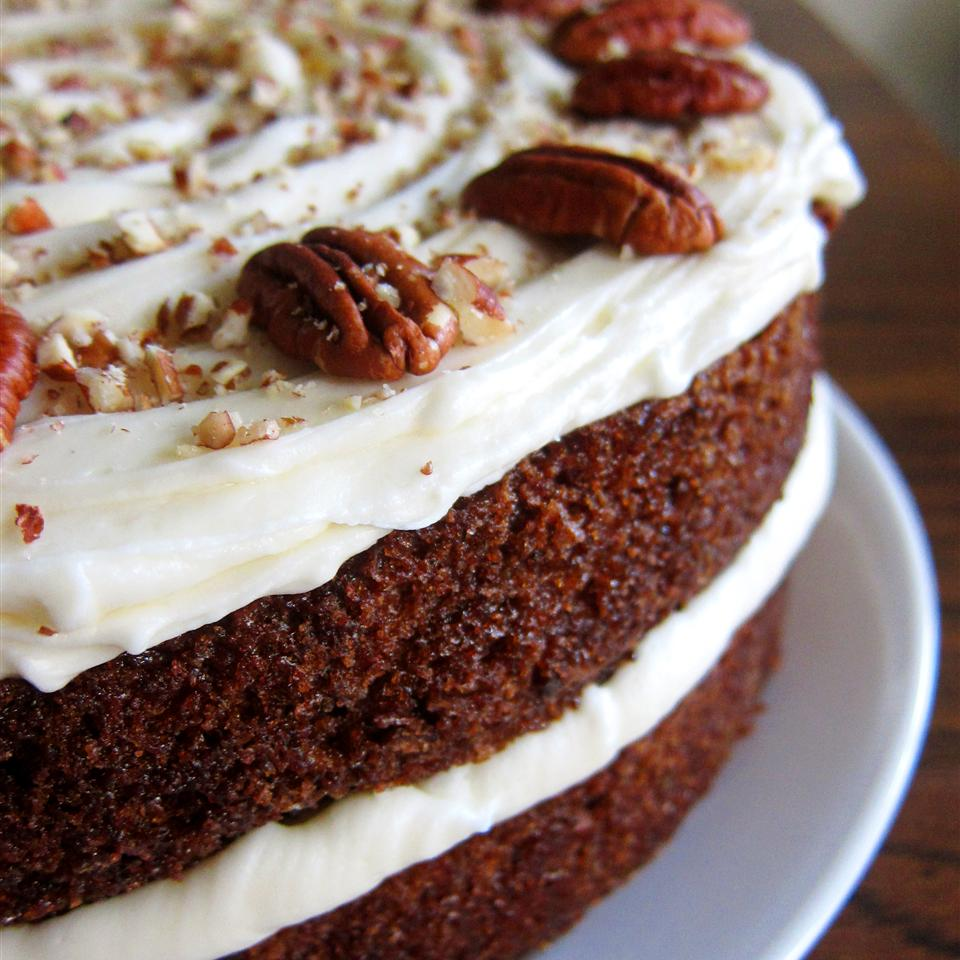 carrot cake with thick layers of frosting and pecan topping