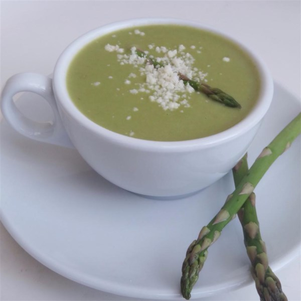 Creamy green soup in a white teacup on a white plate, garnished with an asparagus spear and white cheese crumbles