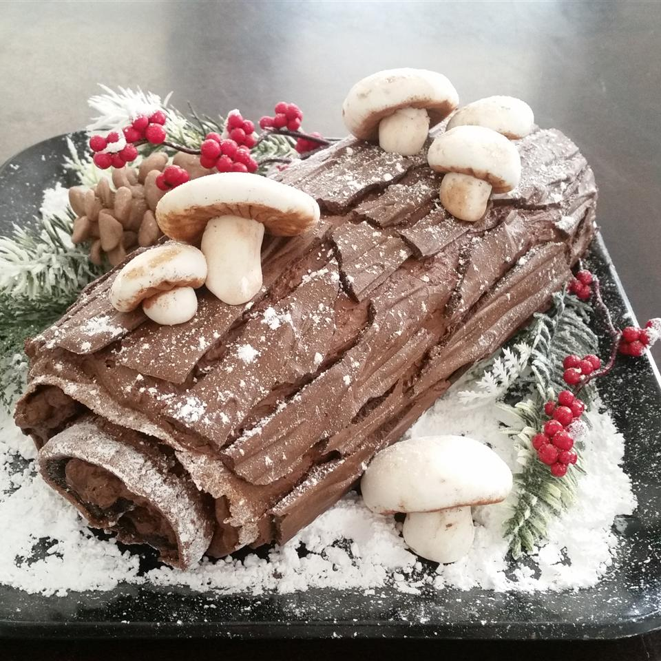 "a Yule log decorated with chocolate ""bark"", meringue mushrooms, and confectioners' sugar snow"