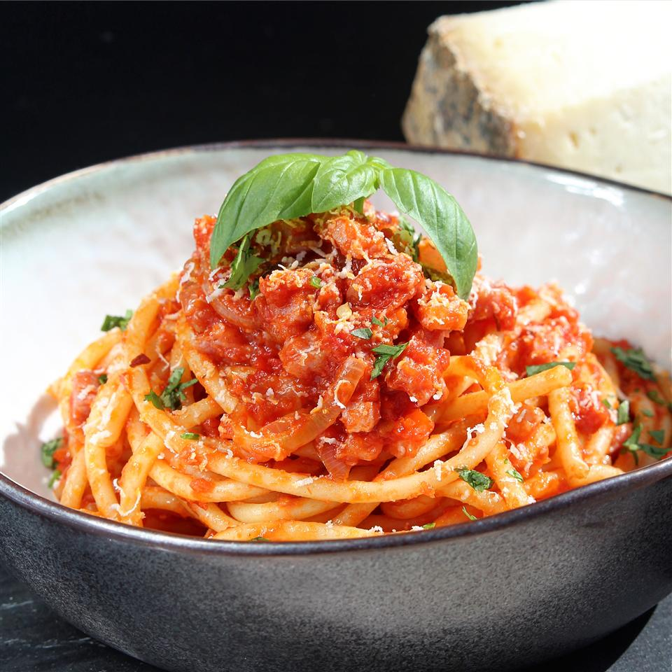 A bowl of hollow spaghetti noodles topped with tomato sauce and fresh basil