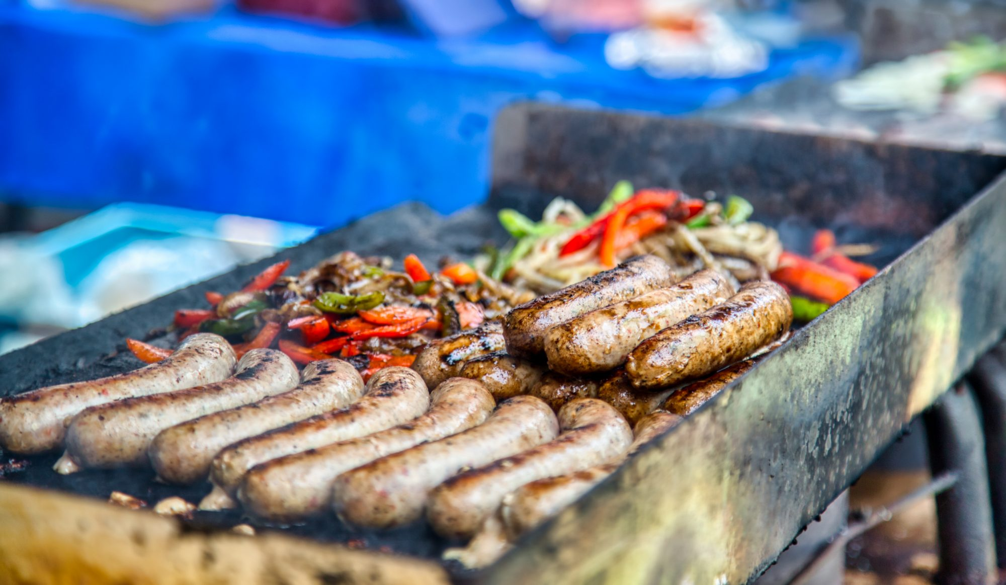 lots of sausage and peppers on the grill at an outdoor market