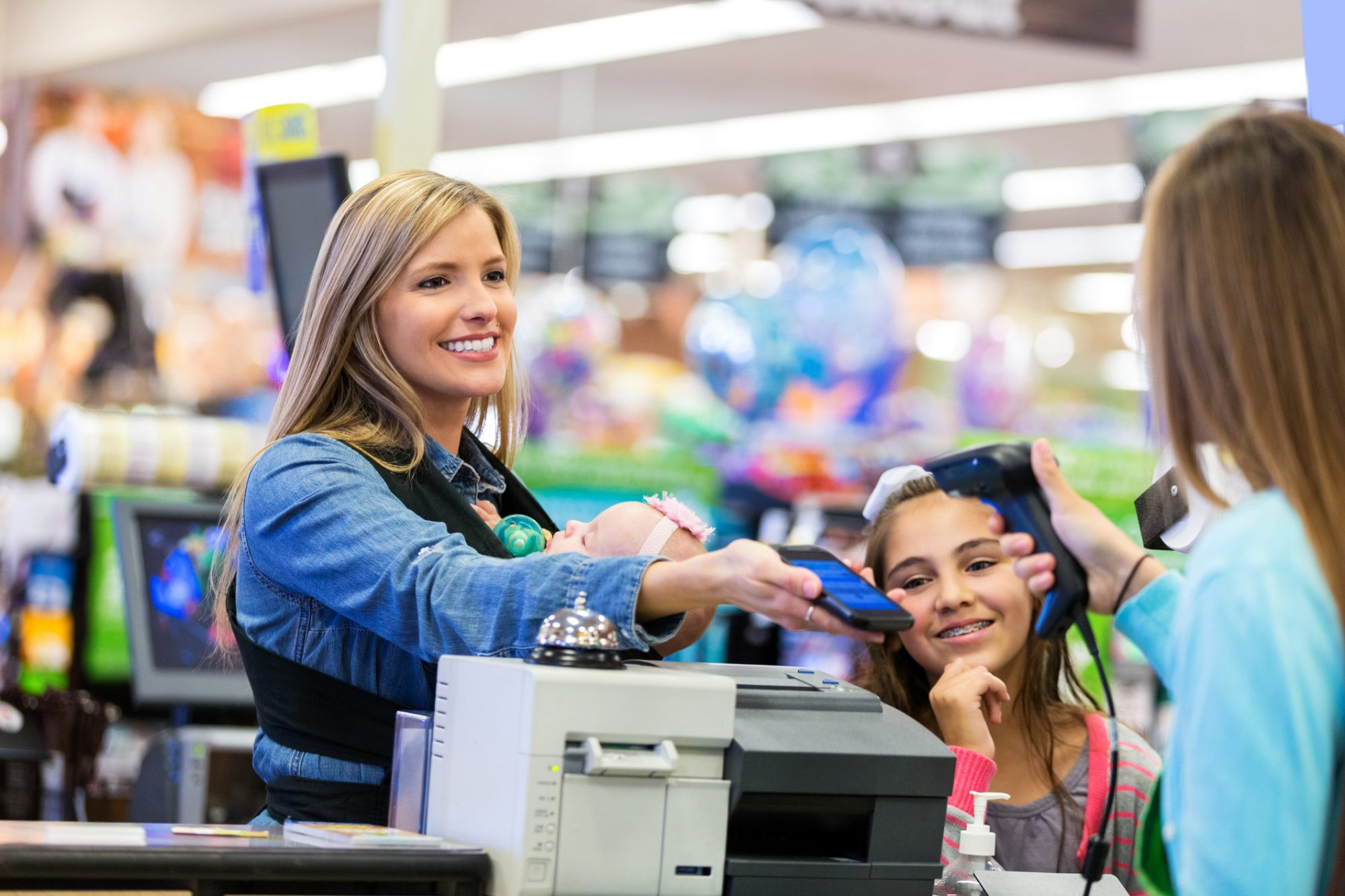 Mid adult Caucasian woman is smiling while using her smart phone to pay for purchases or use coupons in local grocery store. Cashier is using hand held scanner to scan barcode on smart phone. Mother is standing at checkout counter with elementary age daughter. She is wearing her infant in a baby carrier wrap while she shops.