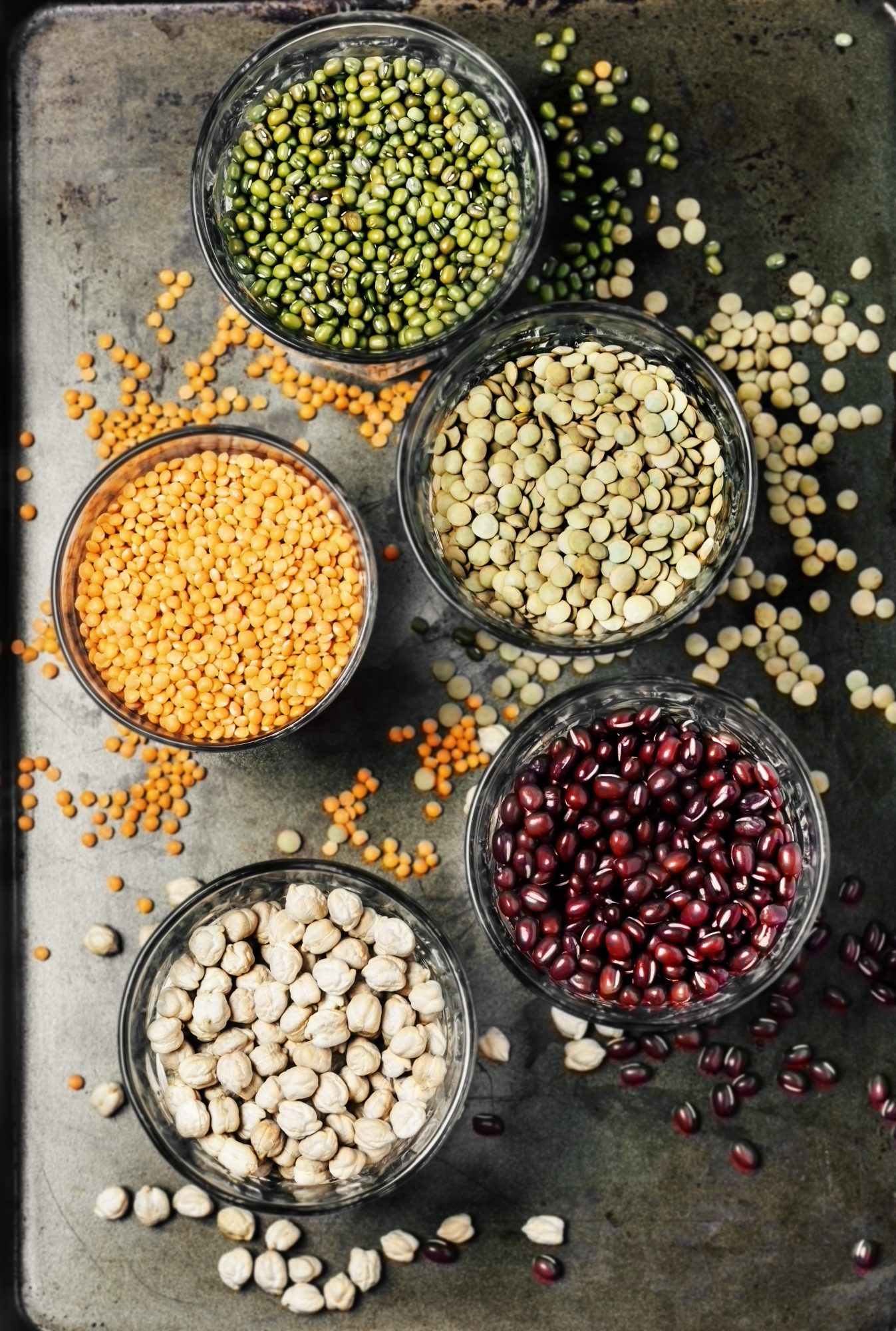 Variety of legumes in glasses on metal background