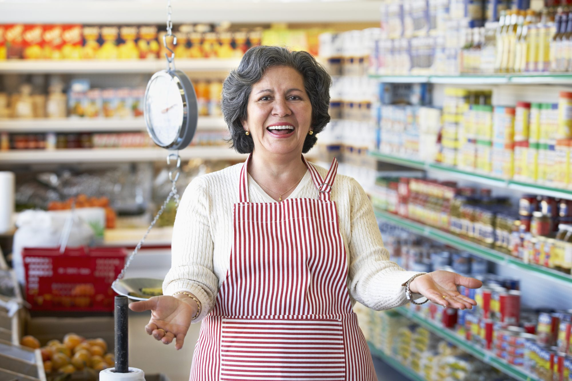 Portrait of welcoming Hispanic grocery store owner