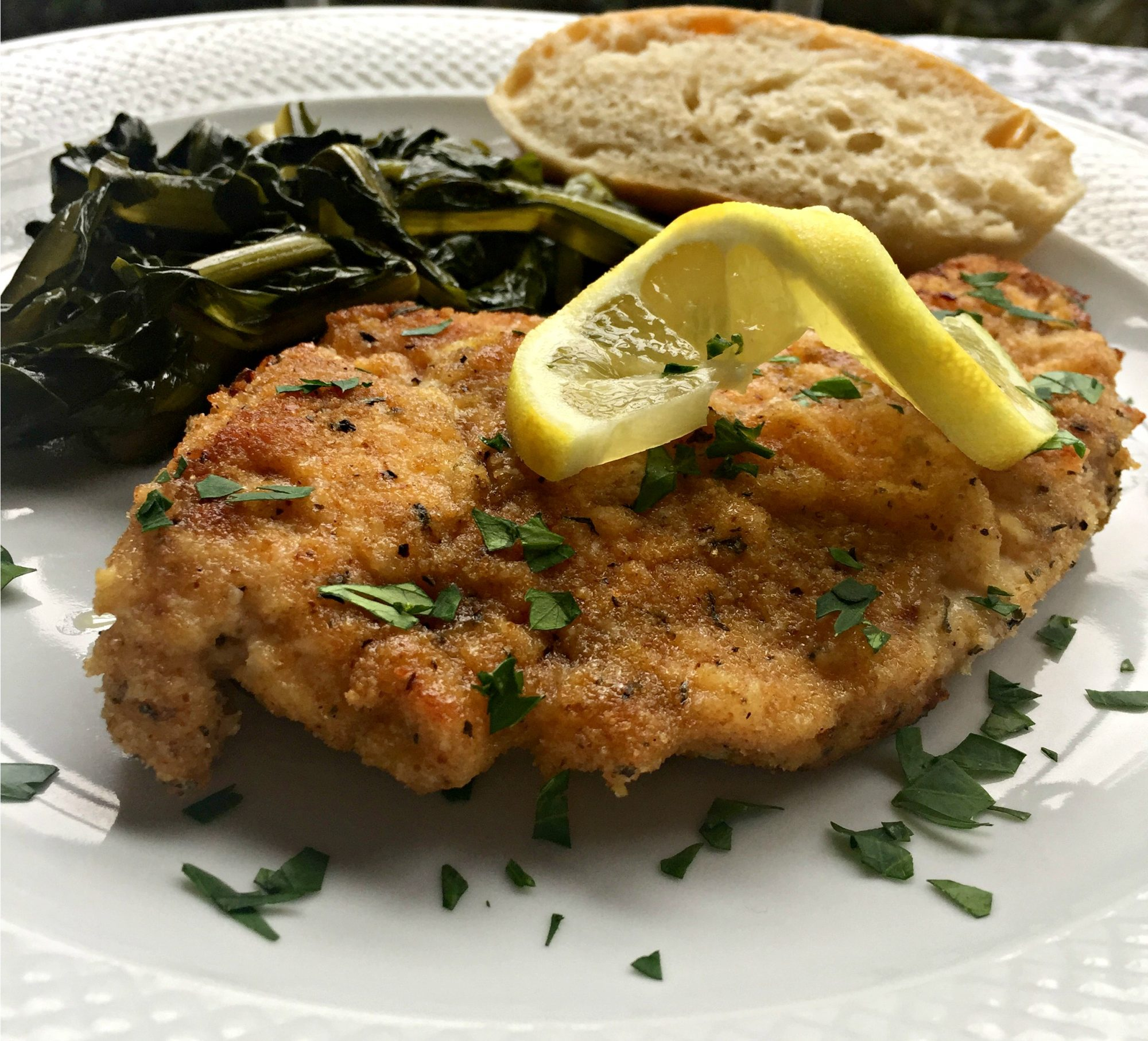 a breaded chicken breast on a dinner plate garnished with a twisted lemon slice and chopped parsley