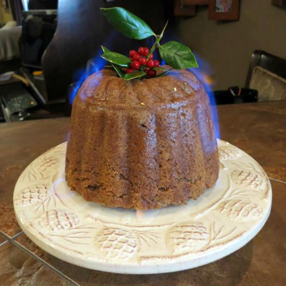a steamed pudding with blue flame, garnished with a holly sprig