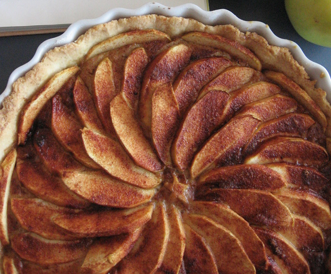 top-down view of browned apple slices fanned out in a spiral pattern in a tart crust
