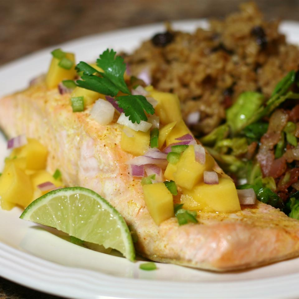 Pour avocado oil, curry powder, and salt over crispy baked salmon before topping it with diced mango, red onion, Serrano pepper, and cilantro.