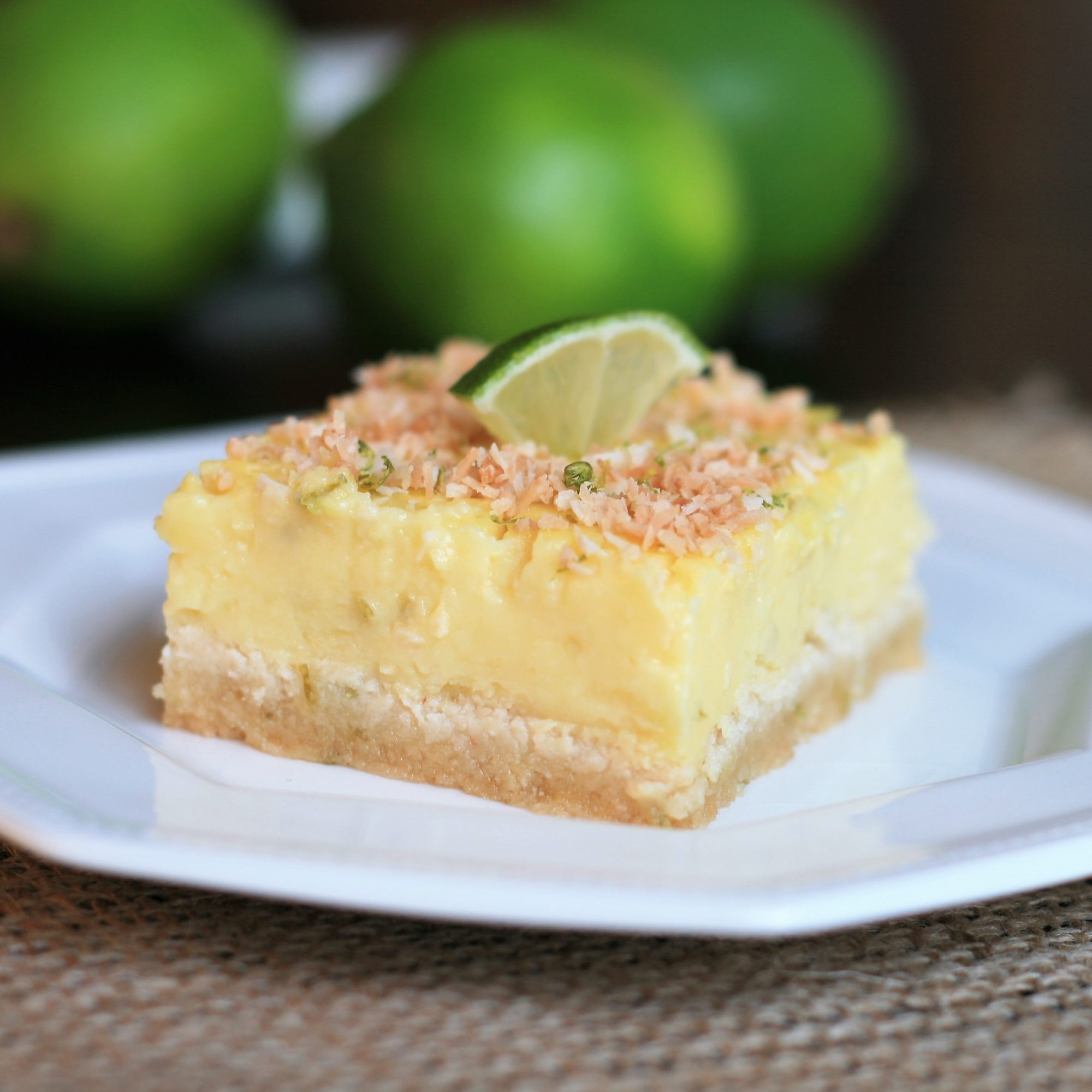 Keto Coconut Lime Bars on a white plate with limes in the background