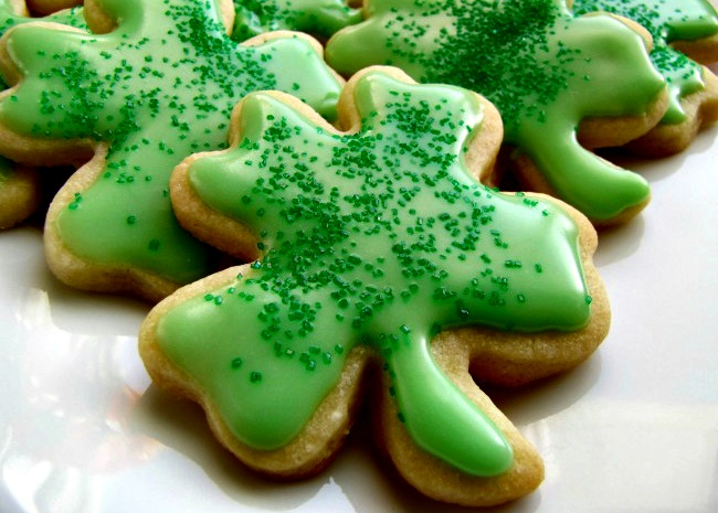 four-leaf clover shapes decorated with green icing and green colored sugar