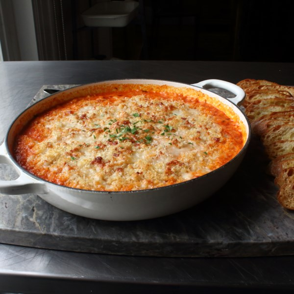 a shallow white enamel baking dish filled with a golden brown cheese appetizer with tomato sauce around the edges