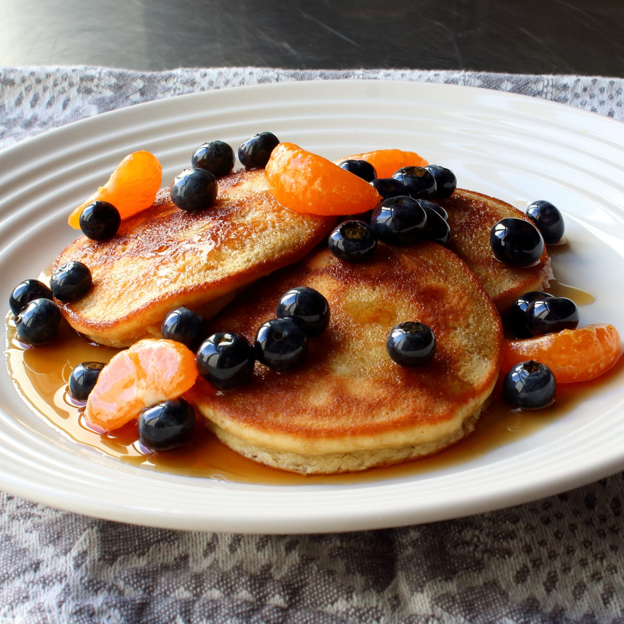 Almond Meal Pancakes with blueberries and mandarin oranges on a white plate