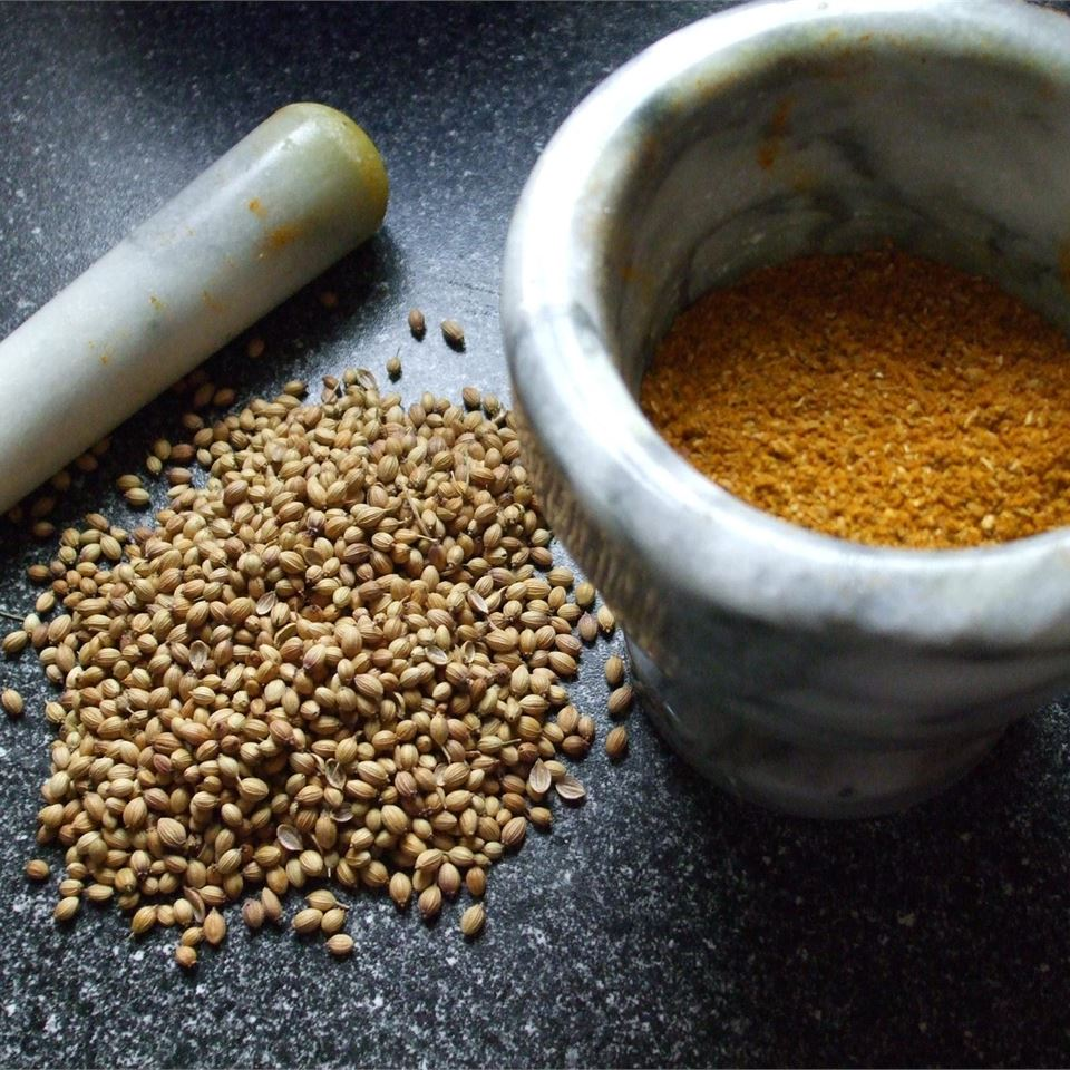 a white marble mortar and pestle with golden powder and coriander seeds on the side