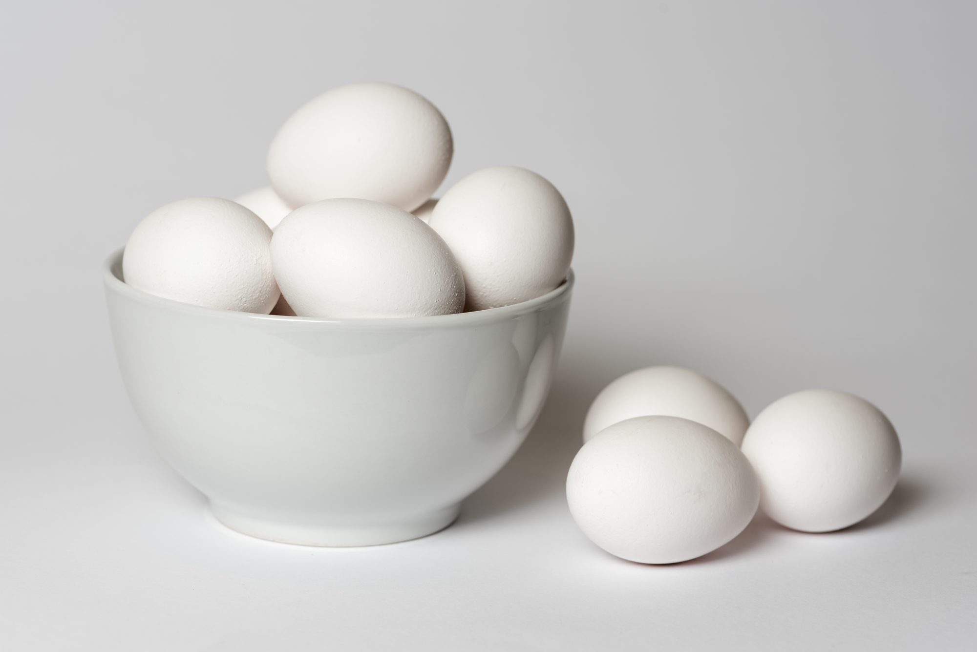 White eggs in a china bowl with three more eggs lying alongside all on a white background
