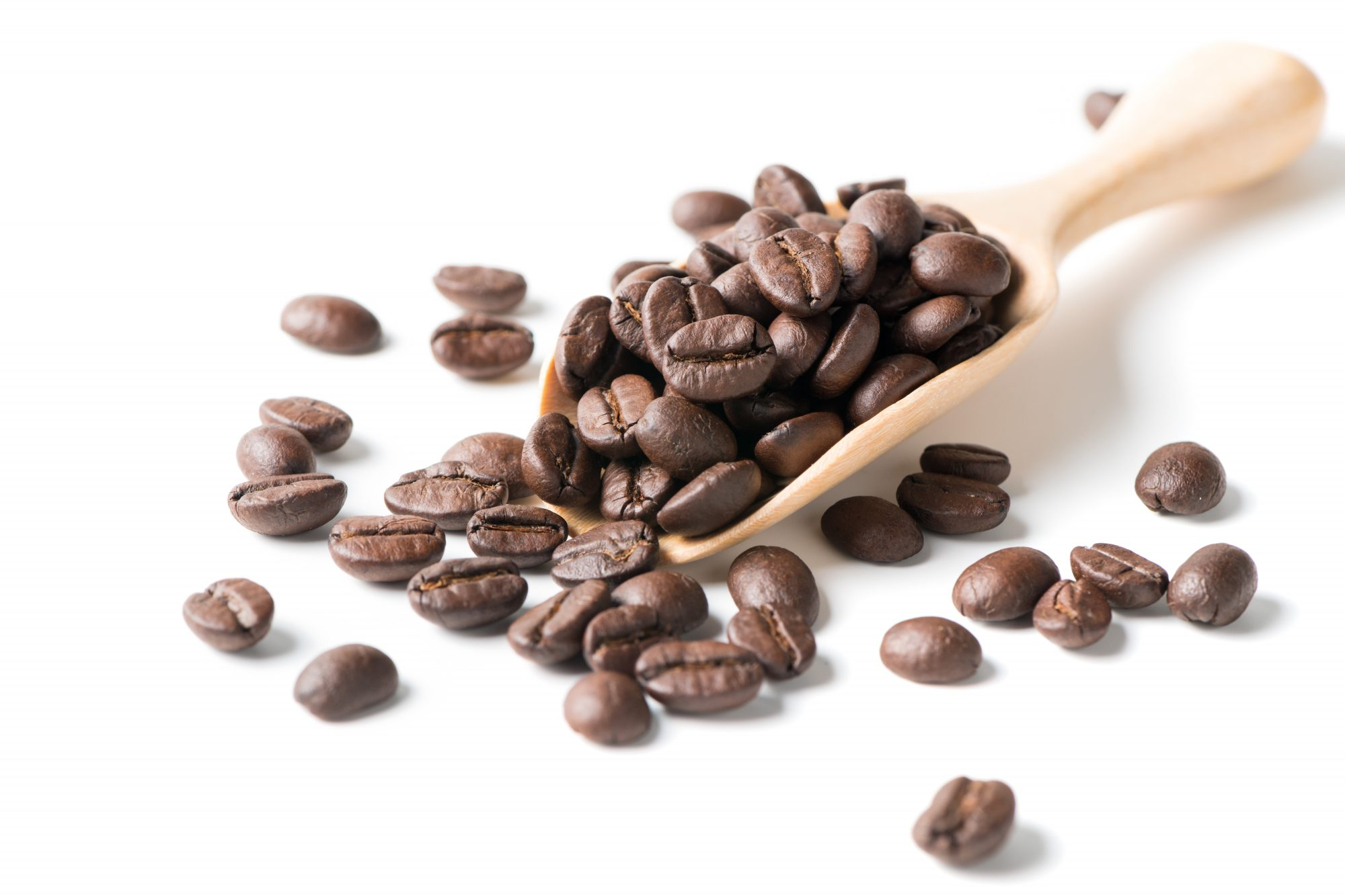 Roasted Coffee Beans In Wooden Spoon Against White Background