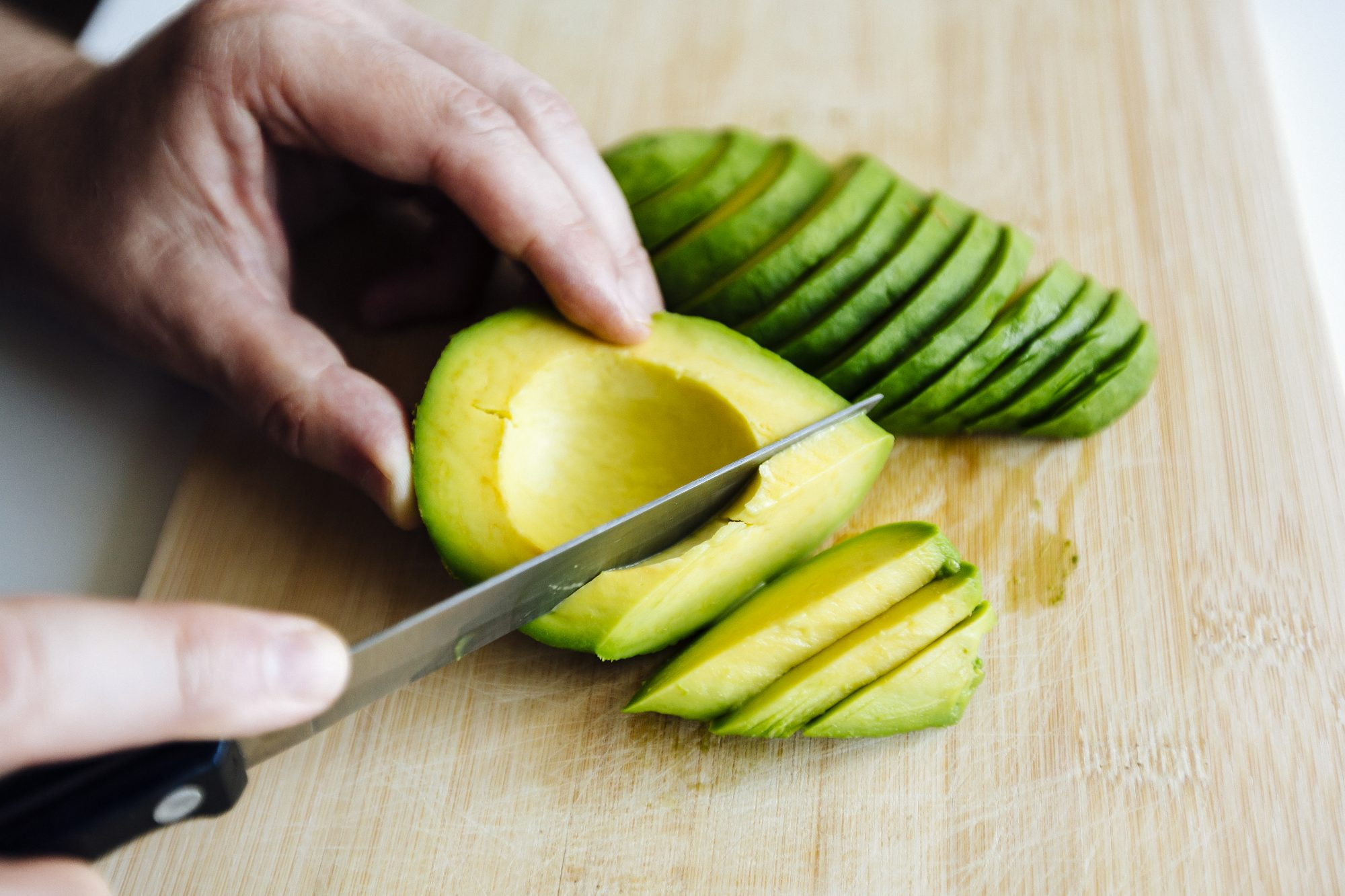 Man slicing avocado with a knife on a cutting board close up