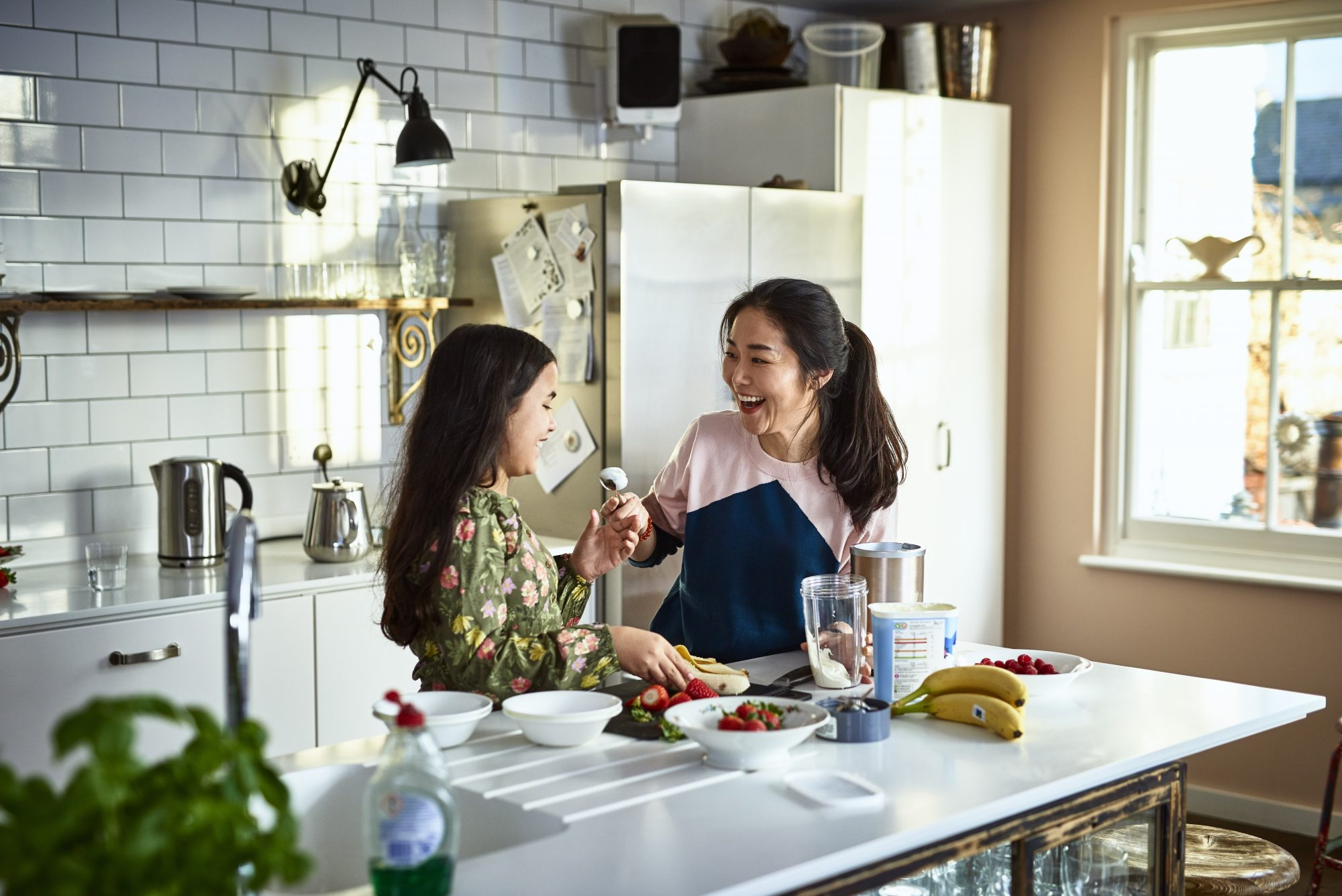 Woman holding yoghurt on spoon towards girl, laughing, threatening to smear food on daughter's face, messing about, having fun, playing, bonding