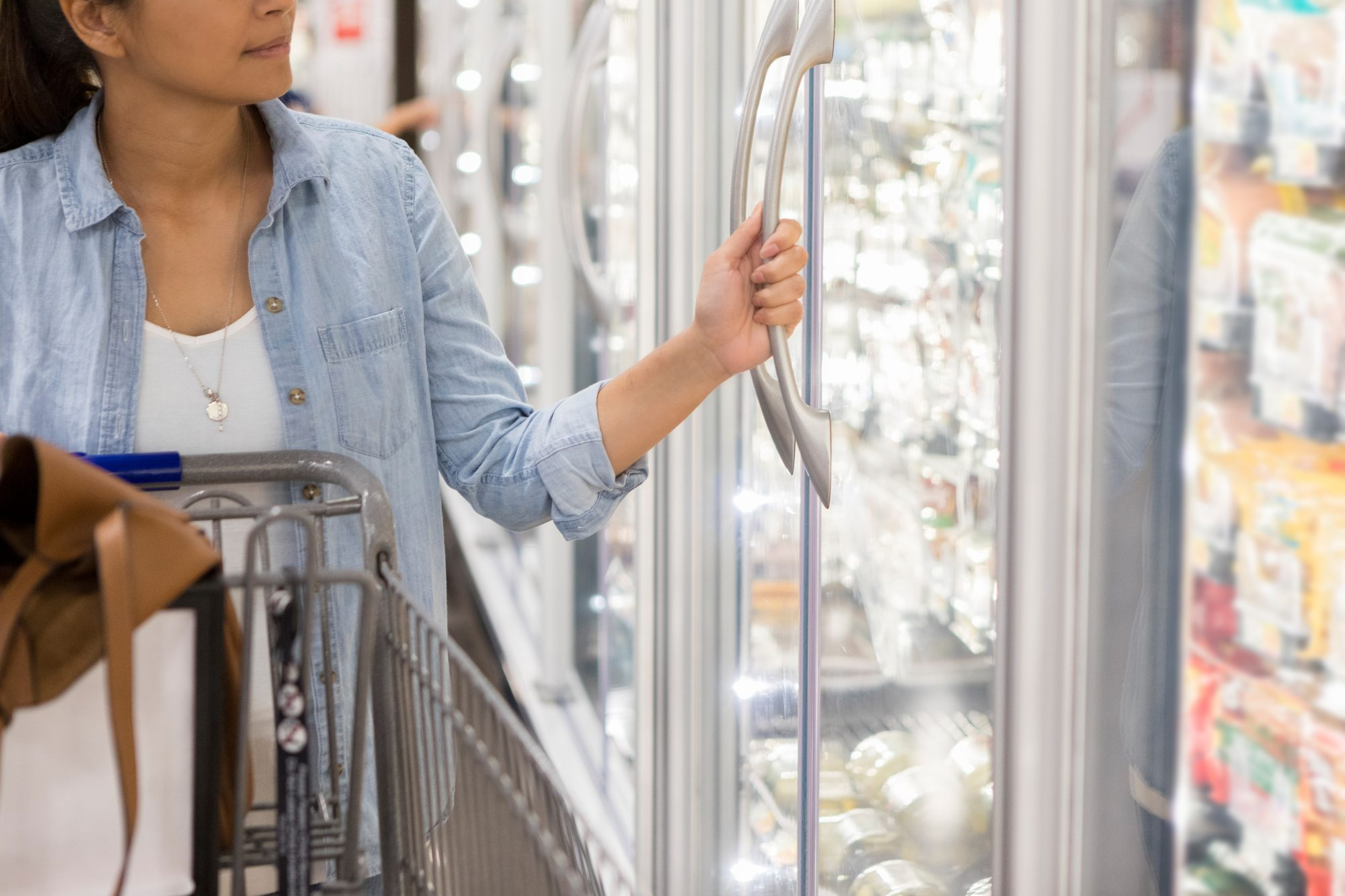 Mid adult woman opens door refrigerator door in supermarket.