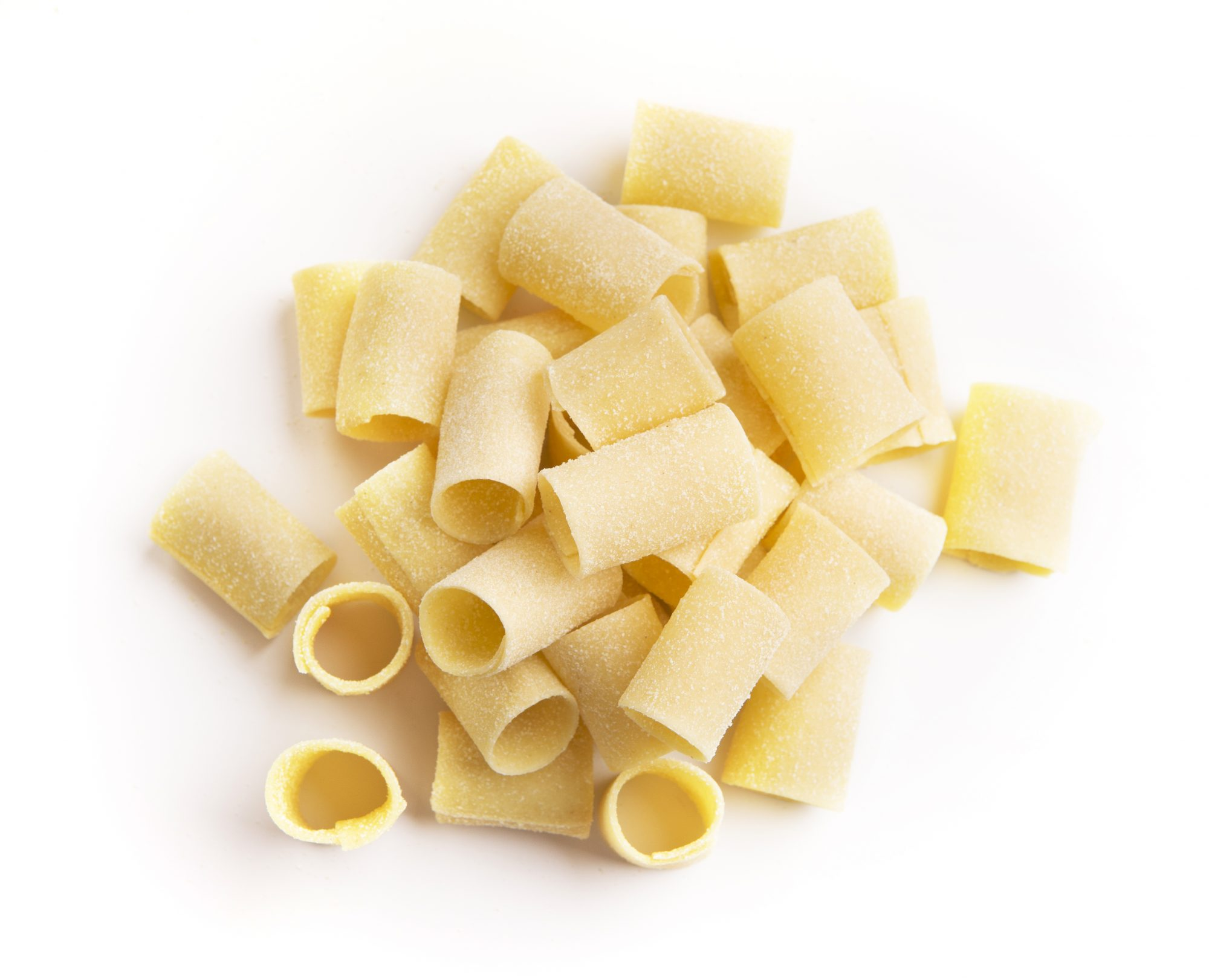 Pile of raw paccheri isolated on white background. Traditional Italian pasta