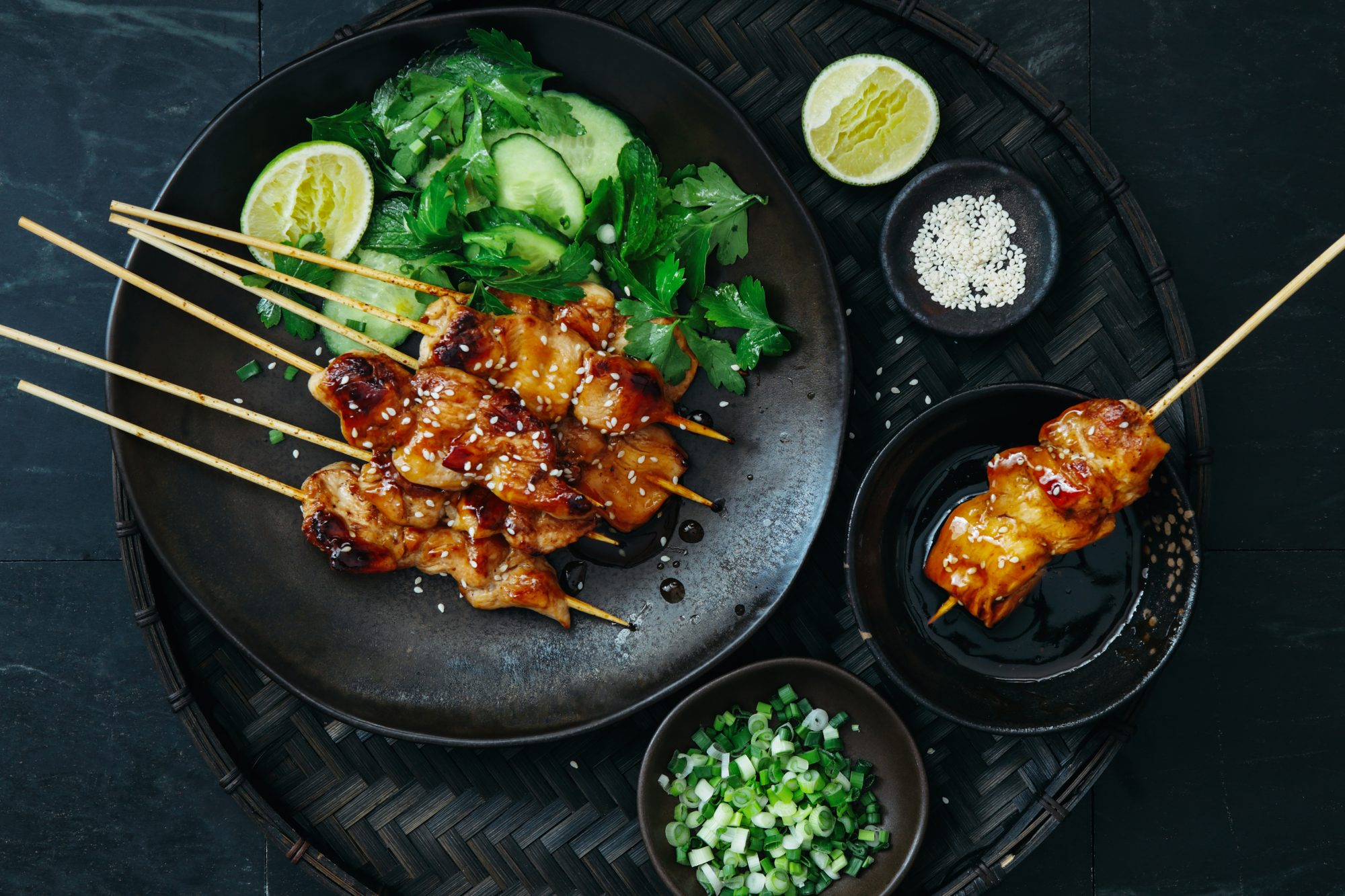 Japanese chicken yakitori skewers with vegetables salad on dark background