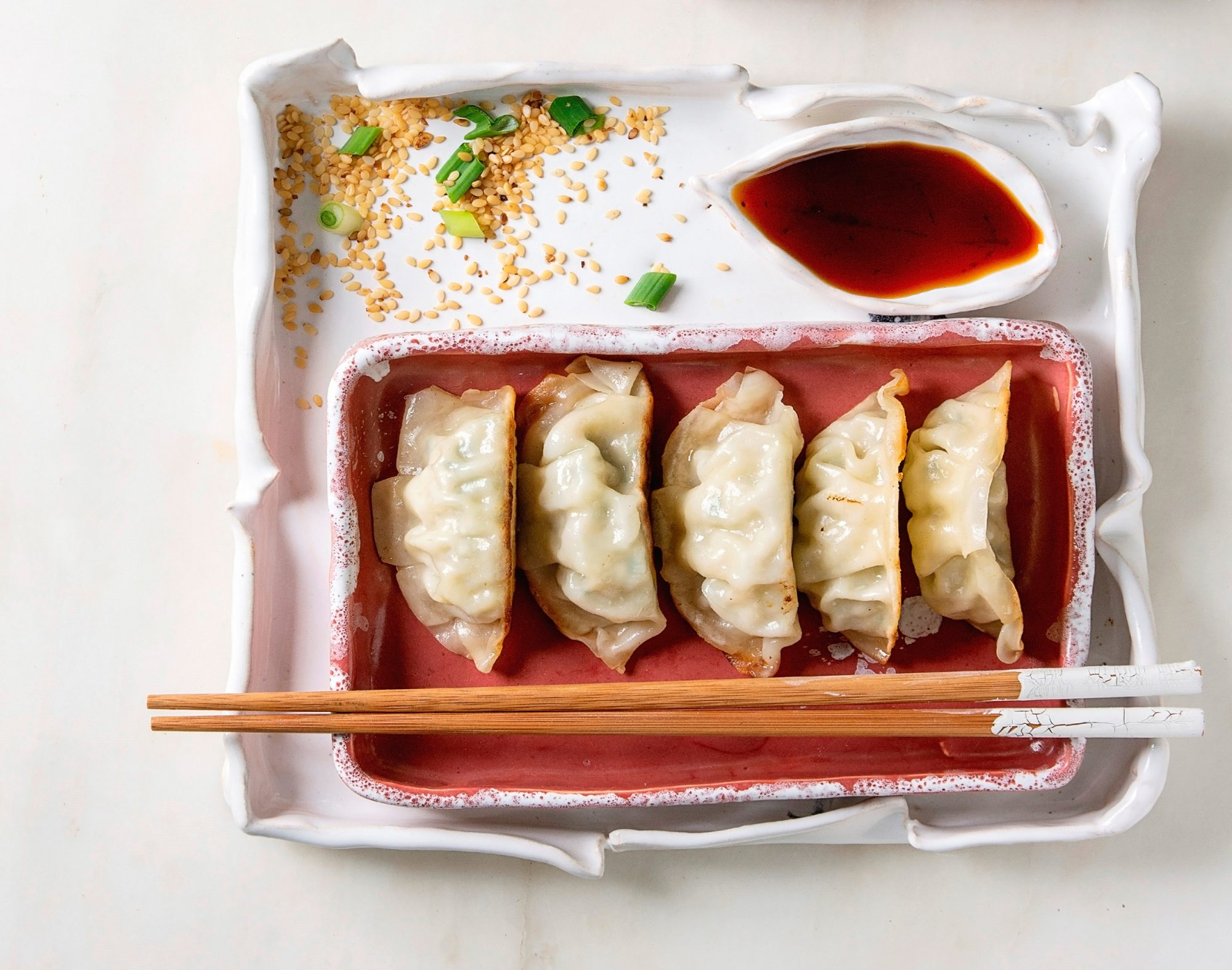 Fried asian dumplings Gyozas potstickers in pink square ceramic plate served with chopsticks, bowl of soy sauce, chopped spring onion over white marble background, Flat lay, space, Asian dinner. (Photo by: Natasha Breen/REDA&CO/Universal Images Group via Getty Images)