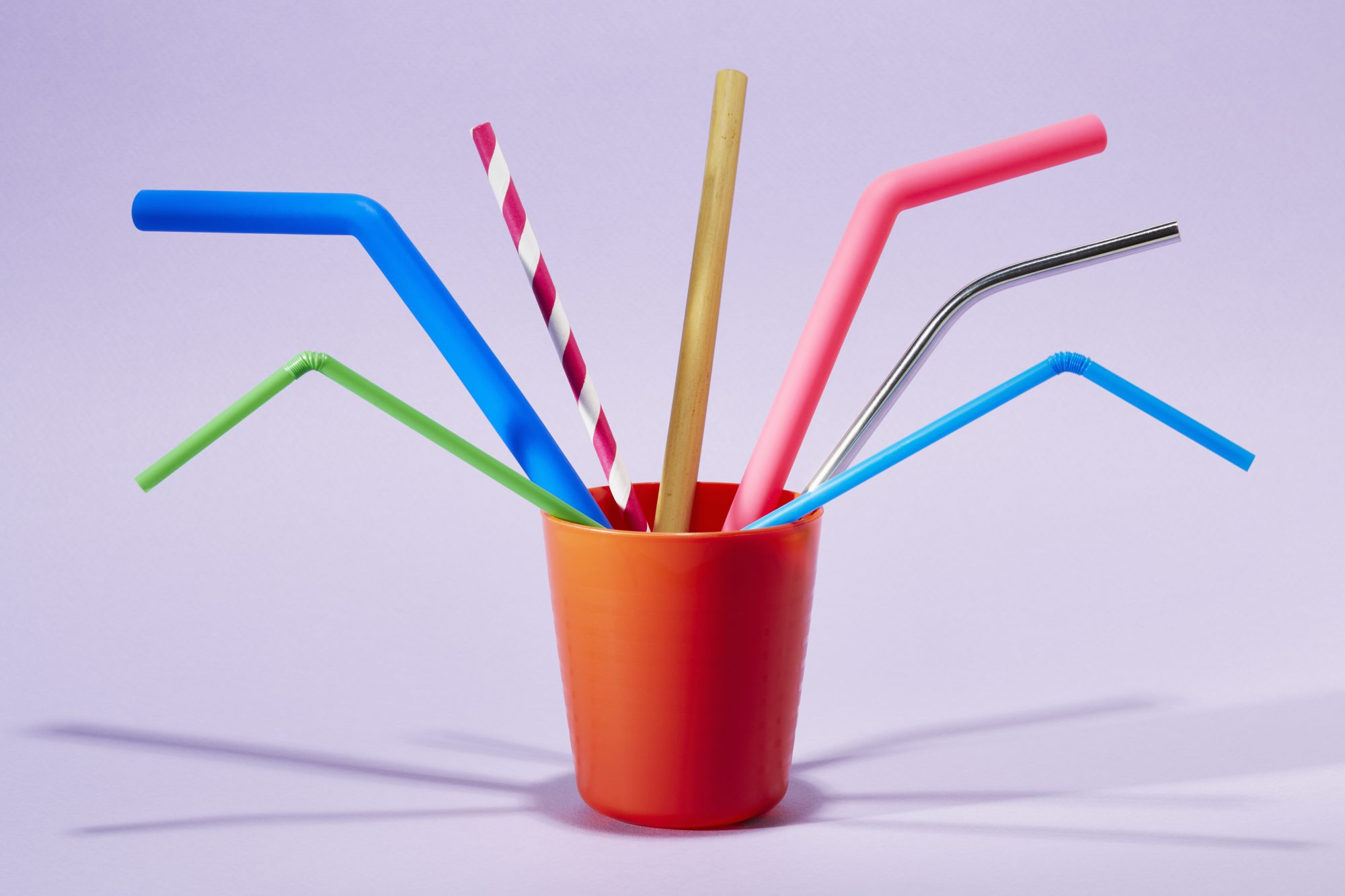 Seven different drinking straws in a cup