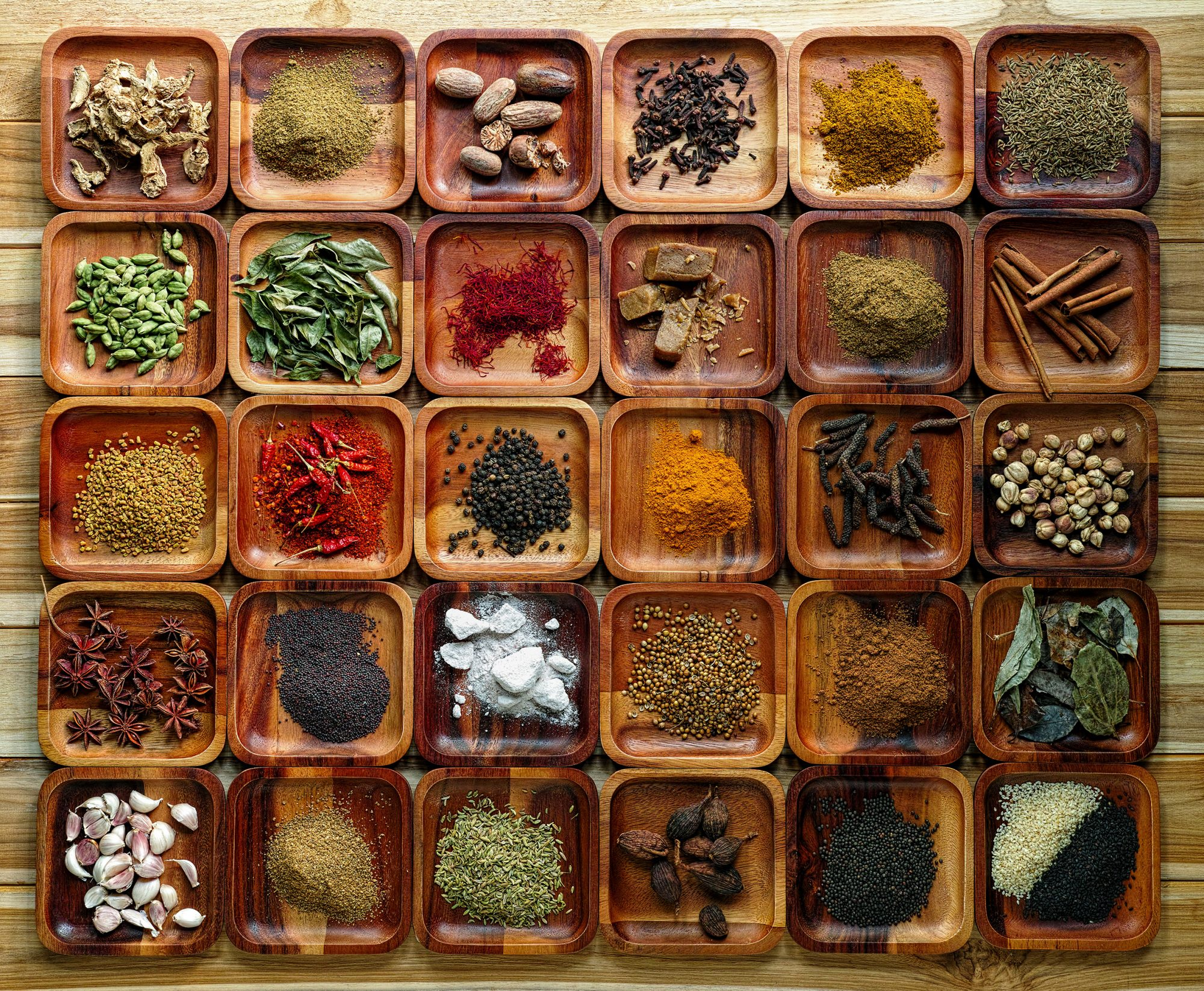 Common Indian herbs and spice ingriedients for preparation of Indian Cuisine in wooden trays on an old rough teak board table.