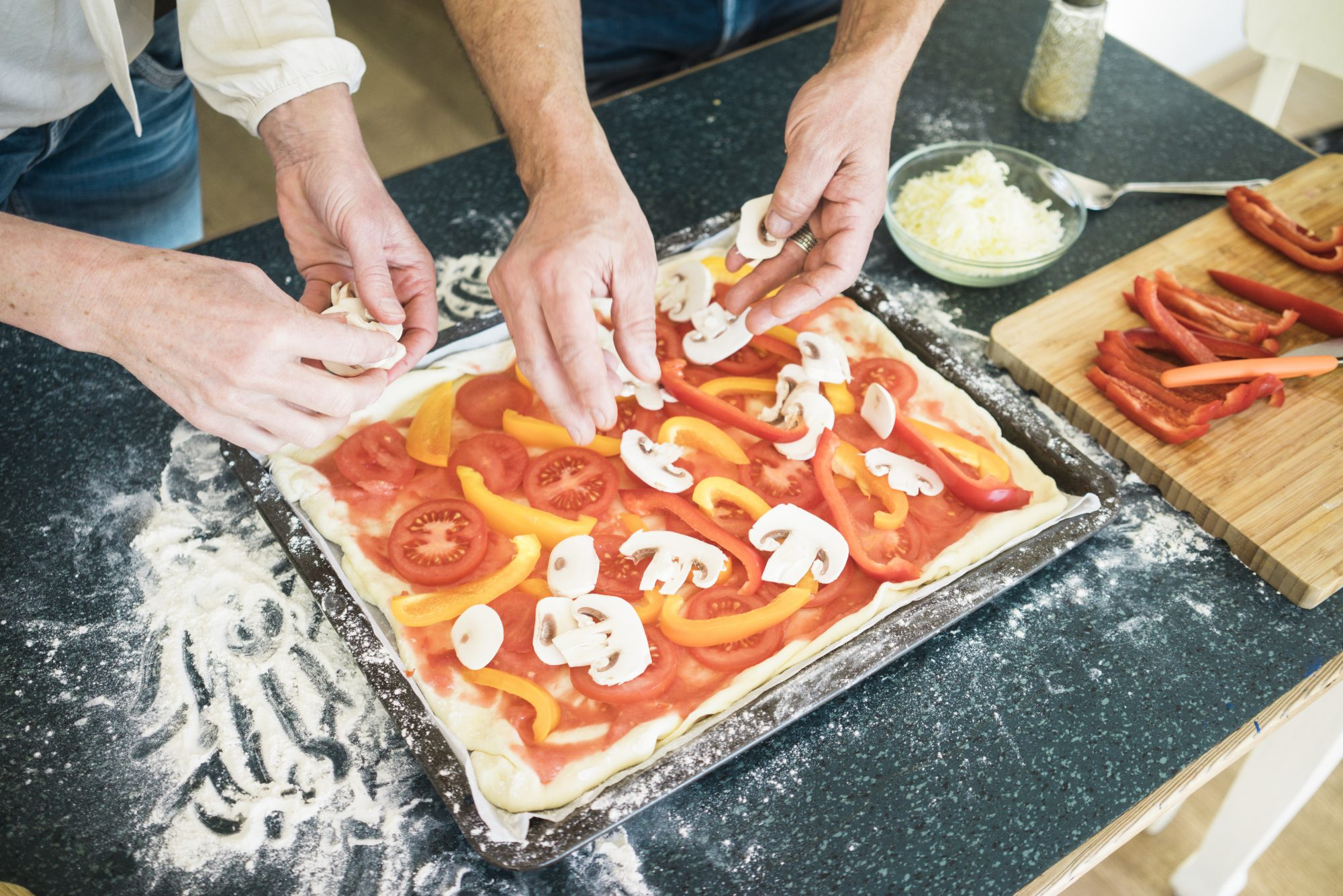 Close-up of couple preparing a pizza in kitchen at home