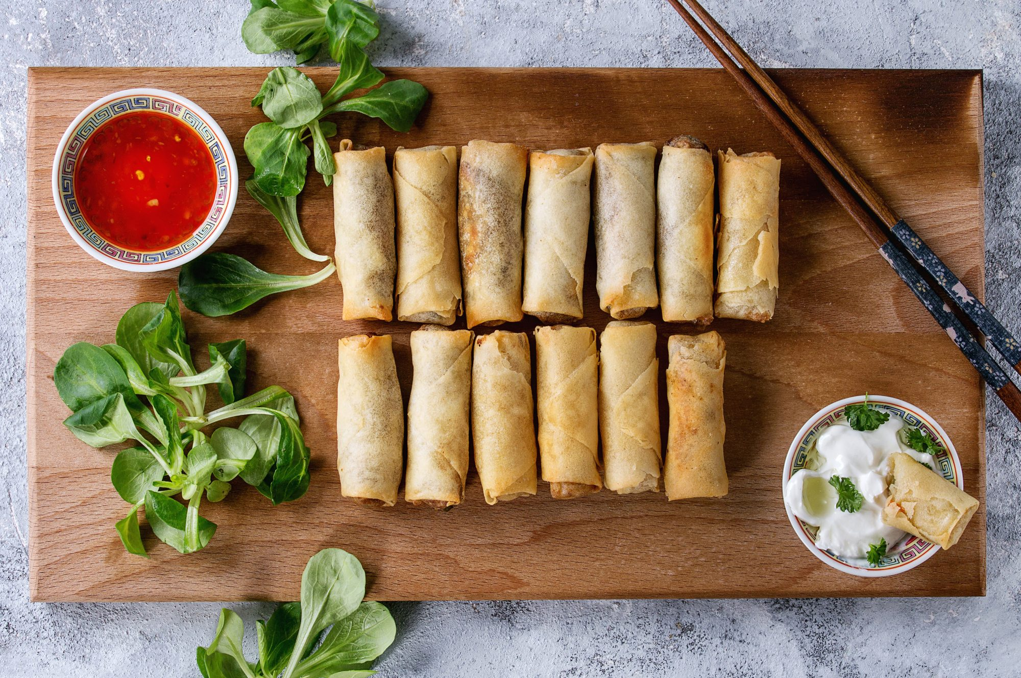 Fried spring rolls with red and white sauces, served on wood serving board with fresh green salad and wooden chopsticks over gray blue texture background. Flat lay, space. Asian food. (Photo by: Natasha Breen/REDA&CO/Universal Images Group via Getty Images)