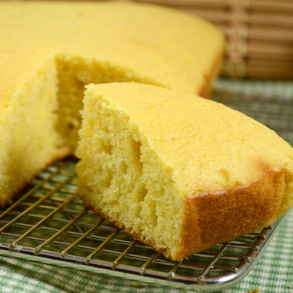 a closeup of a wedge cut from a pan of cornbread on a wire cooling rack